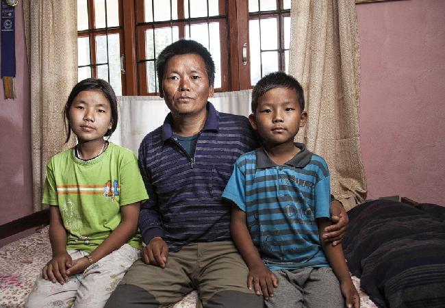 Несмотря на сложный перелом в лодыжке, полученной в июле 2012 года, Лхакпа Рангду вернулся на вершину Эвереста весной этого года, чтобы заработать деньги для своих детей Chhoki (слева, 12 лет), и Мингмы 9 лет.