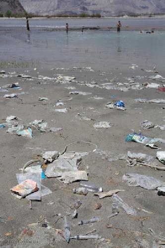 Скарду, разбросанные медицинские отходы у реки Инд. Рядом играются маленькие дети