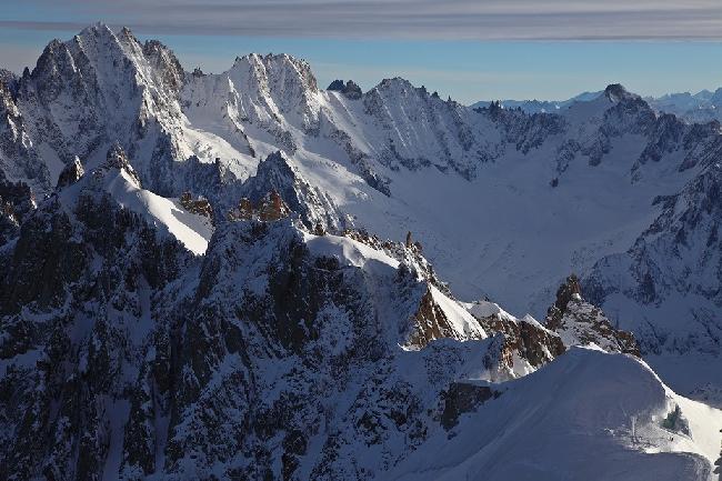 Зимнее утро на Эгюй дю Миди (Aiguille du Midi), Шамони, Франция. Можно разглядеть лыжников, собирающихся спуститься с гребня горы. Фото Jon Griffith