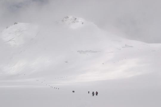 """И не дождавшись хорошей погоды, весь лагерь (а это человек 40) начал спускаться. Спускались в молоко, поначалу мы пытались угнаться за 1-й связкой, но она ушуршала в туман. Когда спустились на плато, развиднелось. Виден маршрут дальнейшего спуска - вверх, на """"груди""""."""