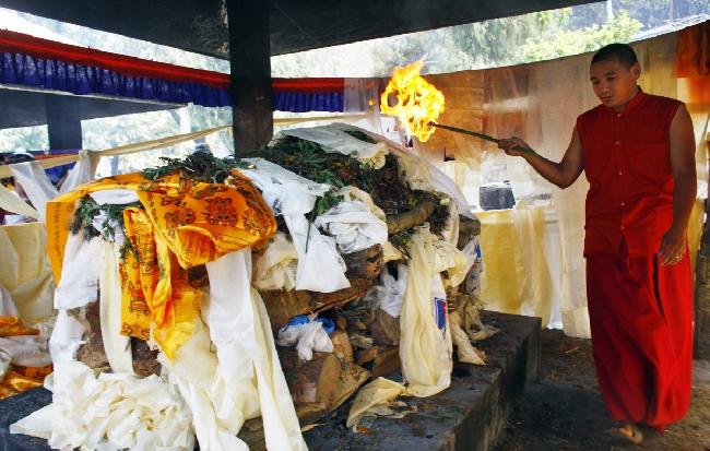 Буддийский монах проводит церемонию погребального сожжения тела погибшего шерпы Ang Kaji Sherpa