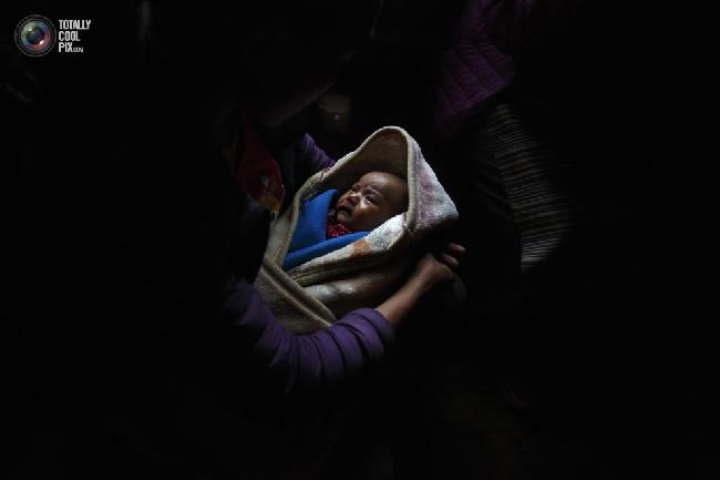 Женщина шерпа держит на руках своего ребёнка, отец которого погиб под лавиной, в районе Кхумбу, Непал. (NAVESH CHITRAKAR/REUTERS)