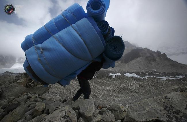 Носильщик уносит матрасы из базового лагеря Эвереста в районе Кхумбу, Непал. (NAVESH CHITRAKAR/REUTERS)