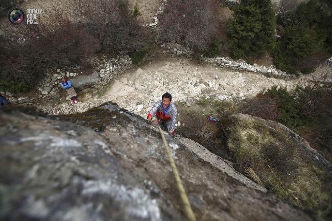 Temba Sherpa поднимается на стену для очистки камня. Намче-Базар. (NAVESH CHITRAKAR/REUTERS)