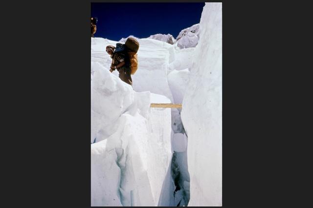 Переход по бревну носильщиков-шерп через глетчер Кхумбу. Из-за крутизны склона там высока опасность ледяных лавин.