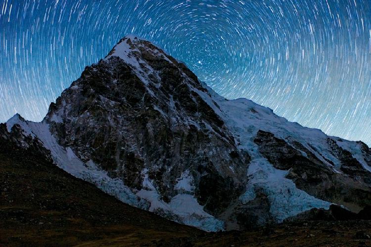 Вершина Пумо-Ри, Непал, 7138 метров. Точка съемки – 5350 метров. 20-минутная выдержка превращает звезды из сияющих точек в треки.  Автор: Алексей Заводский