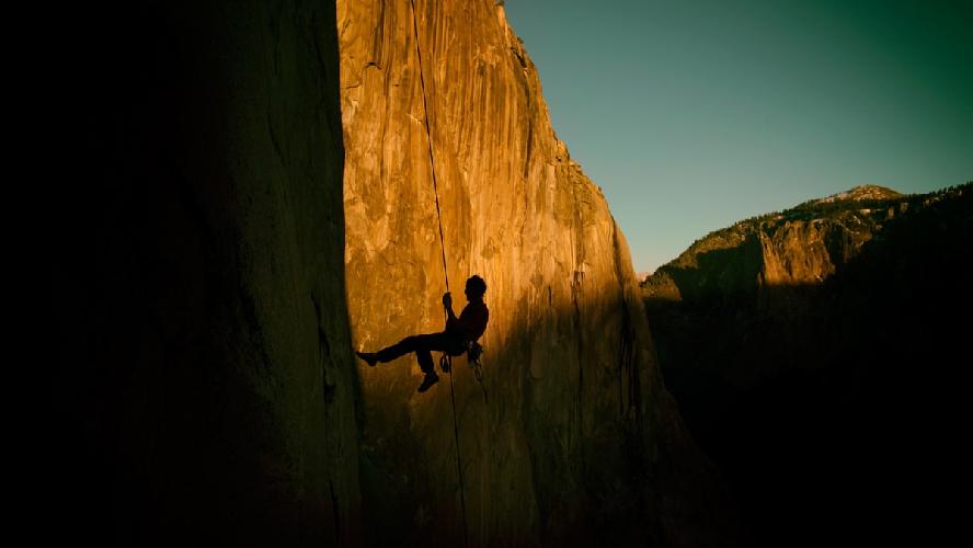 """Заход солнца на Эль-Капитане. Томми Колдвелл (Tommy Caldwell) поднимается по перилам ... В целом же маршрут """"Dawn Wall"""" был так назван из-за того, что первая часть маршрута освещается солнечными лучами в первой половине дня, в то время как вторая часть маршрута остается в тени. Photo: Corey Rich/Aurora Photos"""