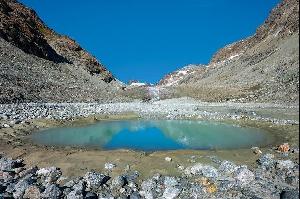 Вокруг камни и щебень, а из под них виднеется голубой лед глетчера Отемма (Otemmagletscher / Glacier d'Otemma). Будучи в длину почти 12 км, этот ледник принадлежит к числу самых больших долинных глетчеров Швейцарии. Перед ним и вокруг него образовался самый обширный в стране регион пастбищных лугов.   Фотографии: Андреас Герт / Andreas Gerth