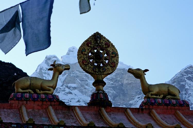 Колесо дхармы и олени на воротах. Видны также молитвенные флаги, на заднем плане шеститысячник Кангтега