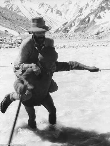 В брод: шерпа несет на себе альпиниста. Британская экспедиция на вершину гималайской горы Камет (Mount Kamet 7756 м). 1931 год. Фото Frank Smythe