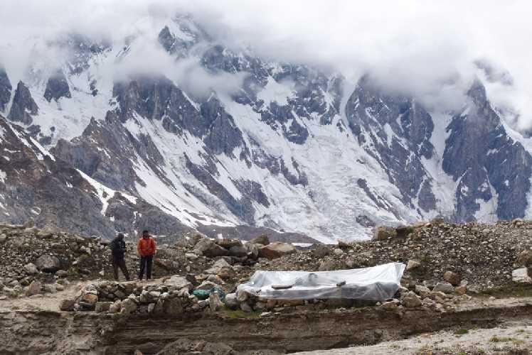 Портеры под тентом на стоянке Накпогоро. За мореной ледник Биафо. Фото Кирилл Белоцерковский