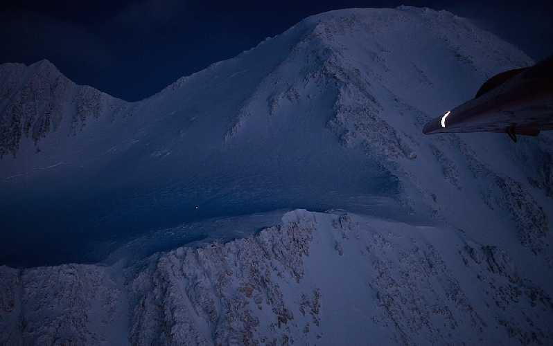 Белая точка на темно-синем ночном фоне горы Денали на Аляске - это Лонни Дюпре на спуске с вершины