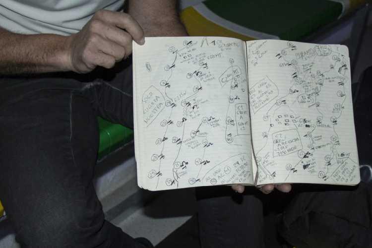 """Алекс Тикон демонстрирует топо-схему маршрута на К2, где расписаны каждые участки провешенной его командой веревки. Слева на тетрадном поле видна надпись: """"solo cuerda nuestra"""" (только наша веревка). Фото Photo: Antonio Fernández"""