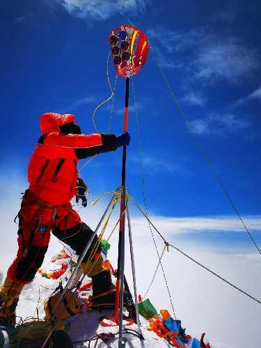 антенну спутниковой системы навигации GNSS и геодезический маркер на вершине Эвереста. 27 мая 2020 года