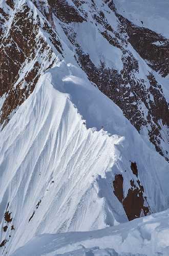 Глядя вверх по маршруту «Shovel Traverse», Вы можете различить всех пятерых участников восхождения. Команда двигалась из лагеря IV в лагерь V, двое альпинистов остановились в лагере V, а трое других преодолели крутой гребень. Фото: Allen Steck