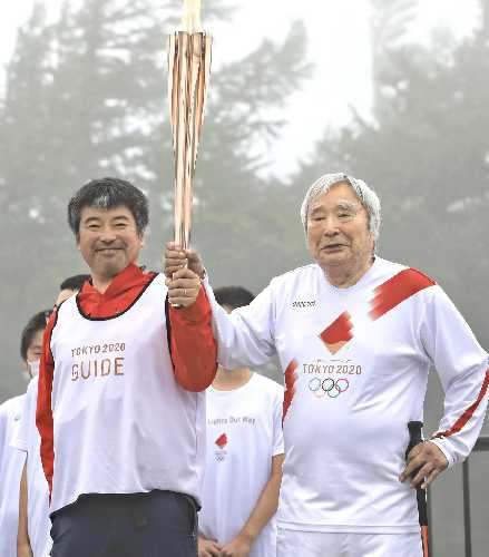Юитиро Миура (Yuichiro Miura) со своим сыном Гота несут Олимпийский огонь на горе Фудзи