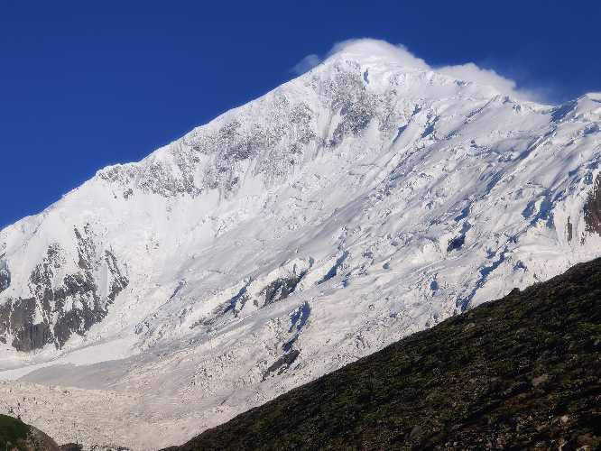 пик Диран (Diran Peak, 7266 метров), белая пирамида, возвышающаяся над зелеными лугами. Фотография: Helias Millerioux