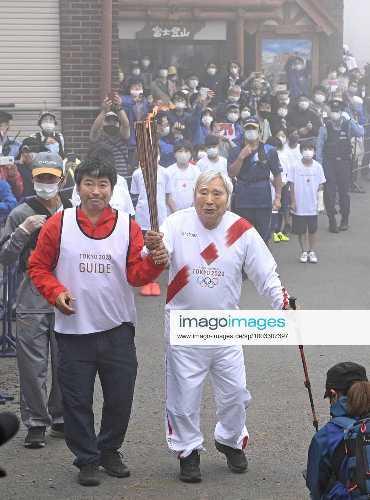 Юитиро Миура (Yuichiro Miura) со своим сыном Гота несут Олимпийский огонь